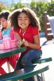 Élève élémentaire se reposant au Tableau mangeant le déjeuner Image libre de droits