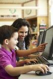 Élève d'école primaire avec le professeur In Computer Class images stock