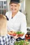 Élève dans la cafétéria de l'école servi le déjeuner par Madame de dîner photos stock
