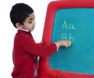 Élève du cours préparatoire apprenant à écrire des alphabets Image libre de droits