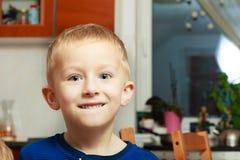 Élève du cours préparatoire blond de sourire heureux d'enfant d'enfant de garçon de portrait à la maison Photo libre de droits
