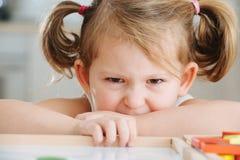 Élève du cours préparatoire de charme jouant avec le constructeur en bois Petite fille jouant avec les morceaux se reliants image stock