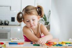 Élève du cours préparatoire de charme jouant avec le constructeur en bois Petite fille jouant avec les morceaux se reliants photographie stock libre de droits