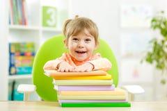 Élève du cours préparatoire mignon de fille d'enfant avec des livres photos stock