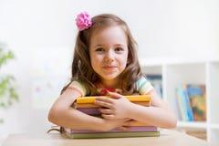 Élève du cours préparatoire mignon de fille d'enfant avec des livres images stock