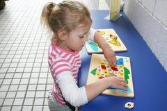 Élève du cours préparatoire remontant un puzzle. Images stock