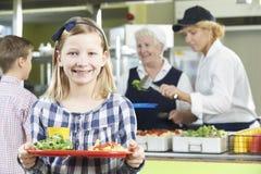 Élève femelle avec le déjeuner sain dans la cantine scolaire Photos libres de droits