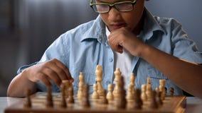Élève junior participant en concurrence d'échecs pensant au-dessus de la stratégie, passe-temps photographie stock libre de droits