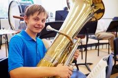 Élève masculin jouant Tuba In High School Orchestra Images libres de droits
