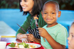 Élèves élémentaires appréciant le déjeuner sain dans le cafétéria Photos stock