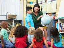 Élèves élémentaires dans la classe de géographie avec le professeur Photo stock