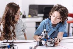 Élèves curieux explorant le robot à l'école image libre de droits