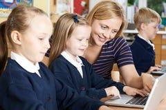 Élèves d'école de Helping Female Elementary de professeur dans l'ordinateur Clas photos libres de droits