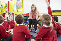 Élèves d'école primaire de Reading Story To de professeur images stock