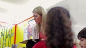 Élèves d'école primaire de Reading Story To de professeur banque de vidéos
