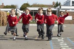 Élèves d'école primaire fonctionnant dans le terrain de jeu Photographie stock libre de droits