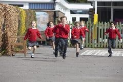 Élèves d'école primaire fonctionnant dans le terrain de jeu Images libres de droits