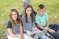 Élèves de la préadolescence d'école en dehors de la salle de classe avec l'ordinateur portable Photos stock