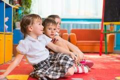 Élèves du cours préparatoire mignons s'asseyant sur le plancher et l'écoute Images libres de droits