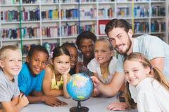 Élèves et professeur regardant le globe dans la bibliothèque Photographie stock libre de droits