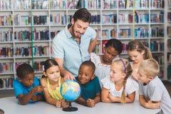 Élèves et professeur regardant le globe dans la bibliothèque Photos stock