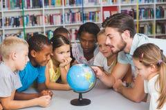 Élèves et professeur regardant le globe dans la bibliothèque Image libre de droits