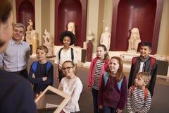 Élèves et voyage d'On School Field de professeur au musée avec le guide Images stock