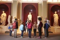 Élèves et voyage d'On School Field de professeur au musée avec le guide photo libre de droits