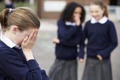 Élèves féminins d'école primaire chuchotant dans le terrain de jeu Image libre de droits