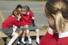Élèves féminins d'école primaire chuchotant dans le terrain de jeu Images stock