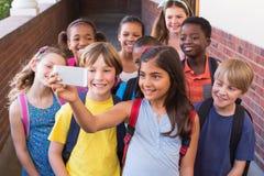 Élèves mignons à l'aide du téléphone portable Image libre de droits