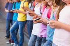 Élèves mignons à l'aide du téléphone portable Images stock