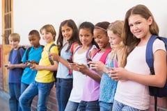 Élèves mignons à l'aide du téléphone portable Images libres de droits