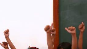 Élèves mignons mettant leurs pouces  banque de vidéos