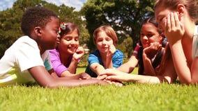 Élèves mignons se trouvant sur l'herbe avec des mains ensemble banque de vidéos