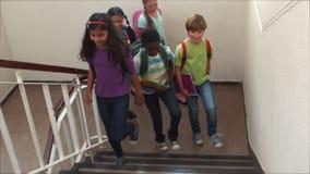 Élèves mignons souriant et marchant vers le haut des escaliers banque de vidéos
