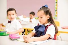Élèves préscolaires écrivant dans une salle de classe image libre de droits