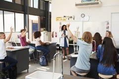 Élèves soulevant des mains dans une leçon de la science de lycée photographie stock
