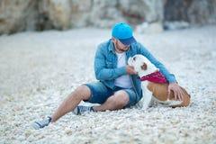 Élégant audacieux bel habillé chez l'homme de jeans dans le chapeau bleu se reposant d'un côté de mer de plage ainsi que le boule Photographie stock