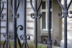 Éléments d'une barrière travaillée en métal noir, derrière laquelle une maison est cachée sur le remblai de Danube photos stock