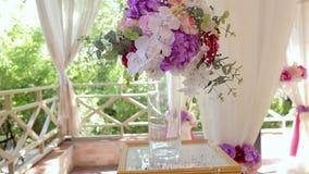 Éléments de conception d'une cérémonie de mariage Un bouquet des fleurs et des orchidées dans un vase en verre banque de vidéos