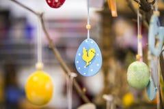 Éléments en bois faits main colorés de Pâques : oeufs, lapins, poussin Pâques lumineuse, résumé, fond brouillé Arbre de Pâques Photos stock