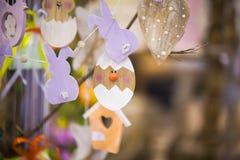Éléments en bois faits main colorés de Pâques : oeufs, lapins, poussin Pâques lumineuse, résumé, fond brouillé Arbre de Pâques Photo stock