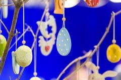 Éléments en bois faits main colorés de Pâques : oeufs, lapins, poussin Pâques lumineuse, résumé, fond brouillé Arbre de Pâques Photo libre de droits
