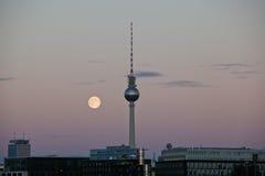 Élévation de lune derrière la tour Alexanderplatz de T.V photographie stock