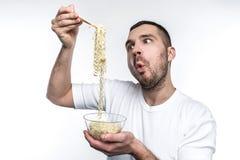 Él adora para comer cada comida basura en un mundo Especialmente él le gusta comer la comida de la cocina oriental El hombre jove Imágenes de archivo libres de regalías