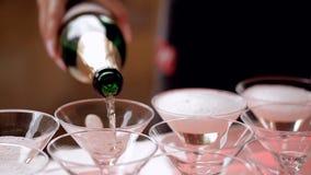 Él camarero vierte el champán en los vidrios, los vidrios del champán en la tabla de buffet, el pasillo del restaurante o el hote almacen de metraje de vídeo