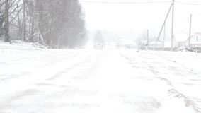 Él coche monta a lo largo del camino nevoso, del invierno y de una ventisca fuerte metrajes