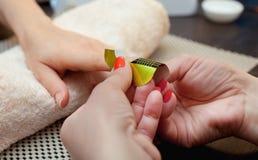 Él domina del esmalte de uñas pone un fijador en el finger antes de hacer el gel de los clavos en el salón de belleza Fotos de archivo