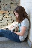 Él es muchacha durmiente con su perro en sus brazos Imagen de archivo